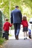 Vader Walking To School met Kinderen op Manier te werken stock afbeeldingen