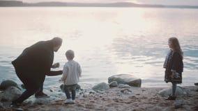 Vader, zoon, dochter op kust De mens die, toont aan jongen en meisje hoe spelsteen het overslaan, makend cirkels op water hurken stock footage
