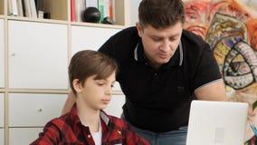 Vaderhorloges op het scherm van laptop die de nessesary taak zoeken die zijn zoon helpen om voor langzame school voorbereidingen  stock videobeelden