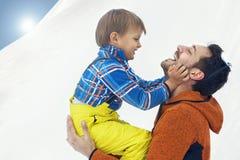 Vaderhulp zijn jonge zoon die hem zijn hand, sneeuw geven royalty-vrije stock foto's