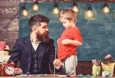 Vaderschapconcept De leraar met baard, vader onderwijst weinig zoon om in klaslokaal, bord op achtergrond te trekken stock afbeelding