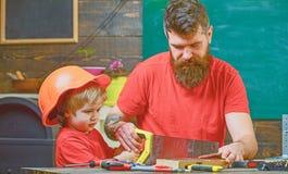 Vaderschapconcept Jongen, kind bezig in beschermende helm die handsaw met papa leren te gebruiken Vader, ouder met baard stock foto's