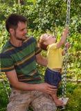 Vaderspelen met zijn kleine zoon op de schommeling Stock Afbeeldingen