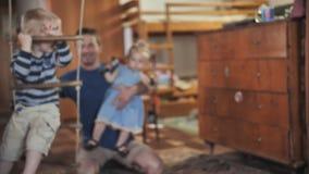 Vaderspelen met zijn zoon en schommeling op een schommeling stock footage
