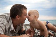 Vaderspelen met zoon op een strand Stock Foto