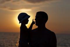 Vaderspelen met zoon tegen een zonsondergang Royalty-vrije Stock Afbeelding