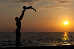 Vaderspelen met zoon tegen een zonsondergang Stock Afbeeldingen