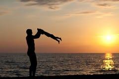 Vaderspelen met zoon tegen een zonsondergang Royalty-vrije Stock Foto's