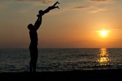 Vaderspelen met zoon tegen een zonsondergang Stock Fotografie