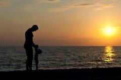 Vaderspelen met zoon tegen een zonsondergang Stock Afbeelding