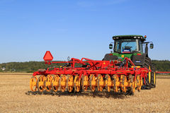 Vaderstad Opus 400 Cultivator and John Deere Tractor on Field. SALO, FINLAND - AUGUST 21, 2015: New Vaderstad Opus 400 cultivator and John Deere tractor on field royalty free stock photos