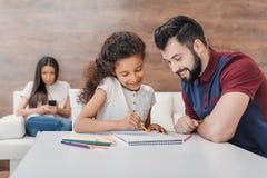 Vadertekening met Afrikaanse Amerikaanse dochter terwijl moeder die smartphone erachter gebruiken Stock Afbeelding