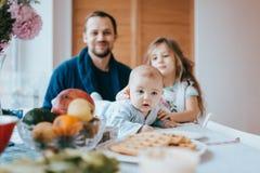 Vaderzitting op een stoel en en zijn kleine dochter die zich naast zijn blik bij de uiterst kleine baby bevinden die op de lijst  royalty-vrije stock foto's