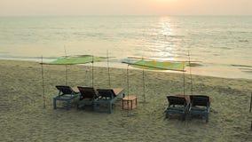 Vadios de madeira azuis vazios da praia sob dosséis na areia na perspectiva do oceano com ondas do mar e trajeto do sol abaixo vídeos de arquivo