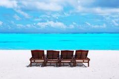 Vadios de madeira do sol na praia do mar Fotos de Stock