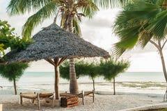 Vadios de Sun na areia branca e em um guarda-chuva das folhas de palmeira dentro imagem de stock