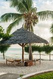 Vadios de Sun na areia branca e em um guarda-chuva das folhas de palmeira dentro fotografia de stock royalty free