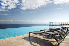 Vadios de Sun por uma piscina da infinidade Foto de Stock