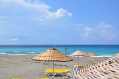 Vadios e parasóis de Sun em uma praia abandonada, o conceito de um espaço perfeito da cópia das férias imagem de stock royalty free