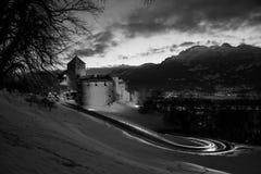 Illuminated castle of Vaduz, Liechtenstein at sunset - popular landmark at night. Black and white stock photography