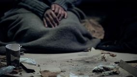 Vagabond covered with dirty blanket sitting on carton, living on street, refugee stock photo
