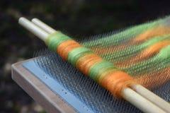 Vagabondaggio arancio e verde della lana su un bordo di mescolamento con due perni di legno Fotografia Stock Libera da Diritti