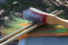 Vagabondaggio arancio e verde della lana su un bordo di mescolamento con due perni di legno e una spazzola metallica Fotografie Stock Libere da Diritti