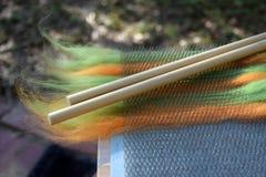 Vagabondaggio verde ed arancio della lana su un bordo di mescolamento con due perni di legno Immagini Stock Libere da Diritti