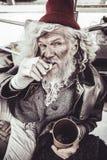 Vagabundo idoso com olhar astuto que come e que olha através da câmera imagens de stock royalty free