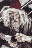 Vagabundo idoso que fala algo ao sentar-se e ao olhar acima através da câmera fotografia de stock royalty free