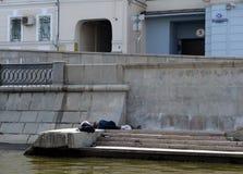 Vagabundos que duermen en el terraplén del canal de Vodootvodny en Moscú Foto de archivo