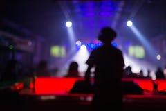 Vage achtergrond: Club, disco die DJ en muziek voor menigte van gelukkige mensen spelen mengen Nachtleven, overleglichten Royalty-vrije Stock Foto's