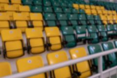 Vage achtergrond Kijkend persoon met gezichtsstoornissen Gele en groene plastic zetels in de tribunes van de complexe sporten stock afbeeldingen