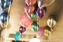 Vage achtergrond met multicolored ballons onder het plafond Feestelijk concept stock foto's