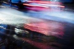 Vage auto in motie het bespatten regenwater het drijven bij nacht royalty-vrije stock afbeelding