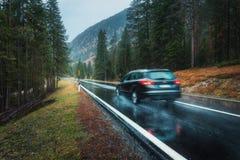 Vage auto in motie op de weg in de herfstbos in regen stock afbeeldingen