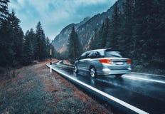Vage auto in motie op de weg in de herfstbos in regen royalty-vrije stock foto