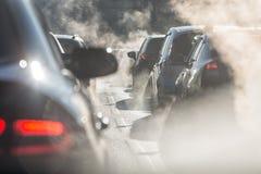 Vage die silhouetten van auto's door stoom van de uitlaat worden omringd royalty-vrije stock foto