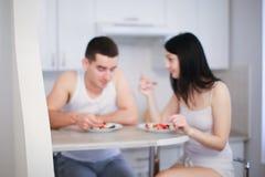Vage foto die van donkerbruine echtgenoot en vrouw die ontbijt in keuken hebben, havermoutpap met bessen eten Stock Foto's