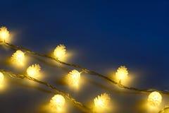Vage gele Kerstmislichten in vorm van kegels in drie rijen op donkere achtergrond, lage diepte van nadruk stock afbeeldingen