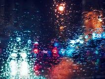 Vage lichte verkeerslichten bokeh met regendalingen op glas Stock Afbeeldingen