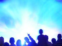 Vage menigte tegen blauw licht Stock Afbeelding