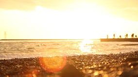 Vage natuurlijke achtergrond overzeese kiezelstenen en vage golven bij zonsondergang stock video