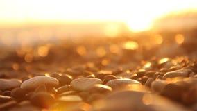 Vage natuurlijke achtergrond overzeese kiezelstenen en vage golven bij zonsondergang stock footage