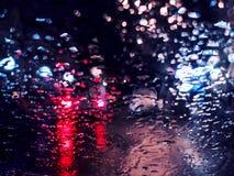 Vage verkeerslichten bokeh met regendalingen op glas Royalty-vrije Stock Foto's