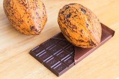 Vagem do cacau e barra de chocolate frescas no fundo de madeira Fotografia de Stock