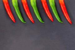 Vagens longas da base do projeto da beira verde vermelha brilhante da peça vegetal do pimento na carcaça preta imagens de stock