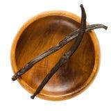 Vagens secadas da baunilha de Bourbon sobre a bacia de madeira vazia Foto de Stock