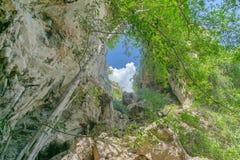 Vagga berg med grottahålet överst, räkningen vid träd, turismläge i sydligt av Thailand arkivfoto