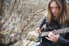 Vagga gitarristen på momenten En musiker med en elbas i a Arkivbilder